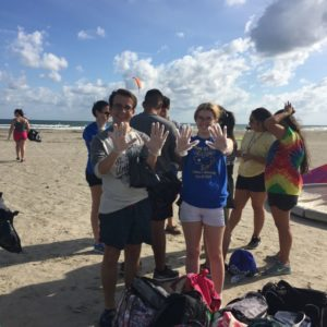 Students pose with gloves on at a beach clean up.