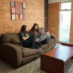 Common room with two students sitting on a couch in Dougherty Hall