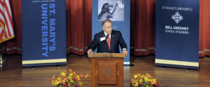 Speaker stands at a podium at a Forum on Entrepreneurship Breakfast