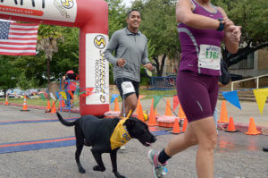 Two 5k runners cross the finish line with their dog
