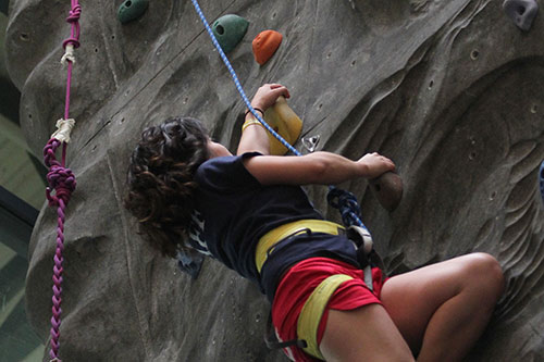 A student climbs the rock wall at St. Mary's AA&CC athletic facility