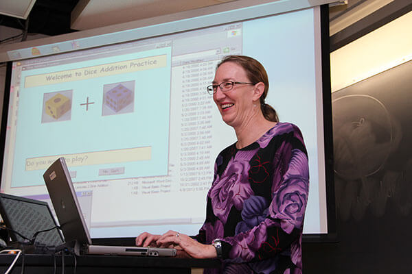 A Computer Science professor smiles during a lecture on software analysis.