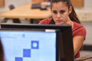 An engineering management student works on a computer design.