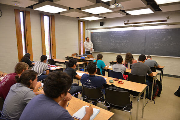 Ian Martines, Ph.D., lectures students on mathematics.