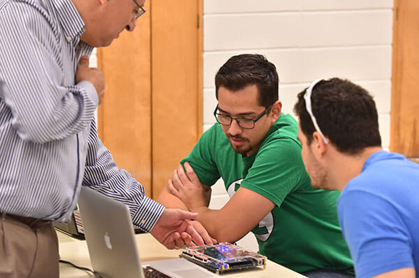 A professor helps students in a software engineering class.
