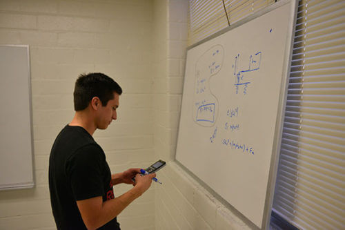Student solves problems in Physics classroom.