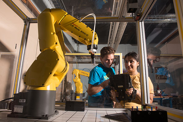 Students operate robotic arm in an Industrial Engineering lab.