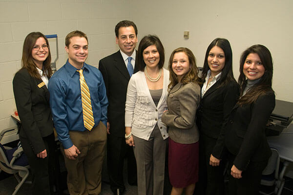 Tom and Leti Contreras with a group of students at the Rattler Enterprises opening ceremony.