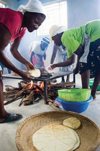 Haitian women making bread over a wood fire
