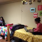 Two girls using their laptops in their Lourdes Hall room