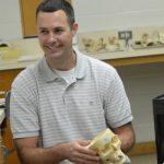 Ted Macrini holding a model of a skull