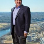 St. Mary's School of Law graduate Terry Mitchell poses in a building showing off the Austin view from downtown.