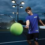 Tennis player Michael Maciel on the St. Mary's tennis courts with a racket hitting a tennis ball toward the camera