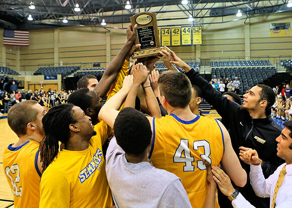 St. Mary's Men's Basketball holding Heartland Conference championship trophy in 2014-2015 season.