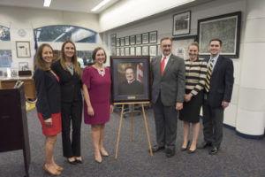 Judge David Ezra stands next to his new portrait.
