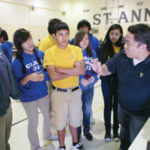 Richard Cardenas, Ph.D, far right, presents a physics experiment to local middle school students.