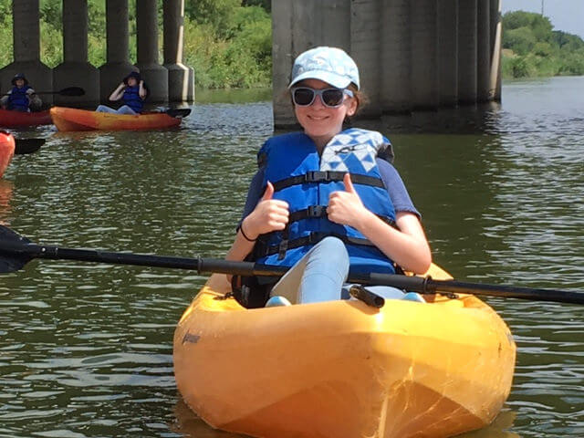 A camper smiles in a kayak at environmental science summer camp in San Antonio