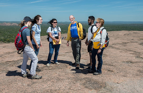 St. Mary's University Environmental Science professors and students standing on the summit of Enchanted Rock.