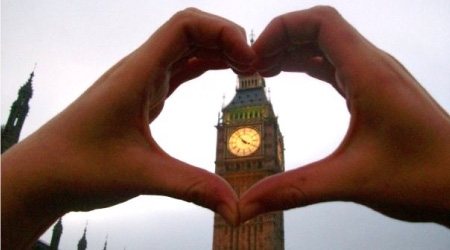 Big Ben showing through a student's hands held together in the shape of a heart