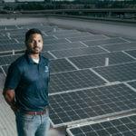 Supratim Srinivasan (B.S. '11) stands among solar panels.