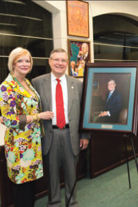 Ronald Herrman and wife Karen stand next to his portrait.