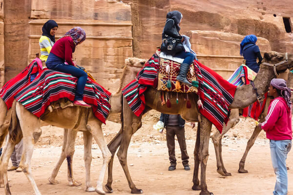 Two tourists riding camels in Jordan