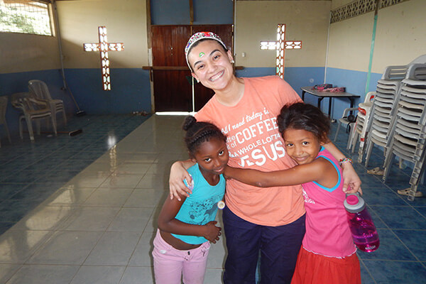 A student hugs two children from her Ecuador service learning study abroad program