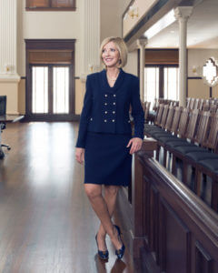 Justice Marion stands in the historic courtroom.