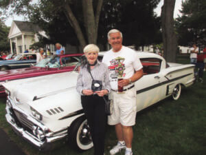 John and Peggy Sieffert stand with trophies at a car show.