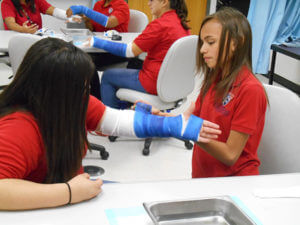 A female camper wraps a fellow camper's arm in medical tape