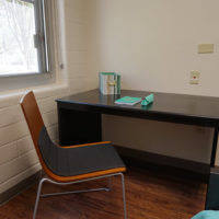 Desk with a chair pulled toward the camera in a Chaminade bedroom
