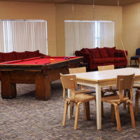 Donohoo Hall common room featuring a pool table, couches and dining area