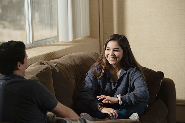 Female student sitting in a common room smiles