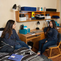 Two roommates face each other, talking in their room