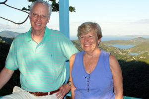 Jim Drought poses on a balcony overlooking a water view with Anita Branch